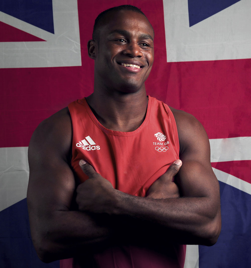 Chev posing with UK flag behind, red outfit